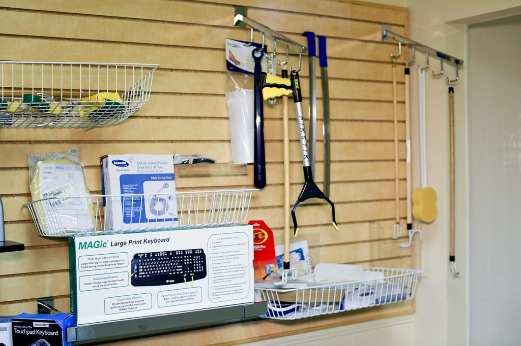 This picture shows a wall display of different self-care assistive devices along with a large print keyboard