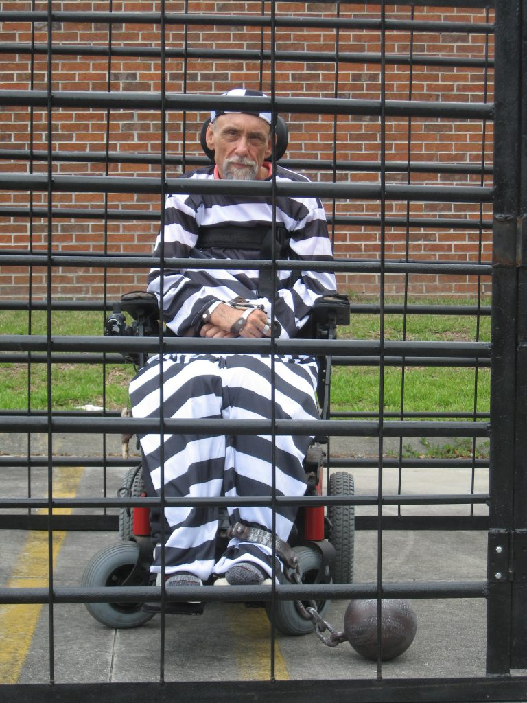 Picture of Bob Habas behind prison bars and dressed like a prisoner
